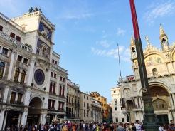 7. On the left is the Torre dell'Orologio (The Clock Tower), which was constructed in the fifteenth century. The most prominent feature is the blue-and-gold clock face which indicates the hour of the day, displayed in Roman numerals. On the right is the Bascilica di San Marco, which is known for its domes and mosaic decorations.