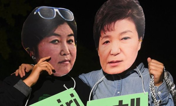 Protesters in Seoul wear masks depicting South Korean president Park Geun-hye, right, and her confidante Choi Soon-sil (Jung Yeon-Je/AFP/Getty Images).