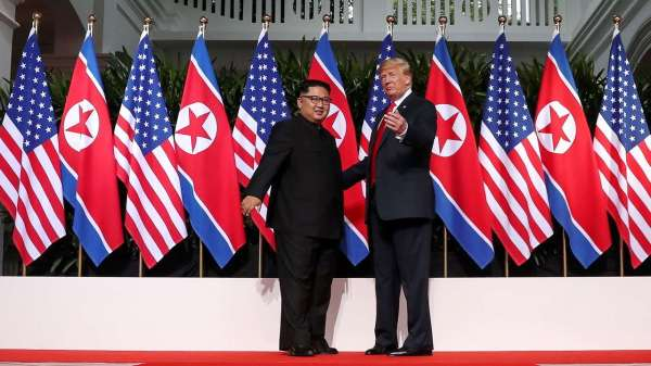 Taken from http://static.dnaindia.com/sites/default/files/styles/full/public/2018/06/12/692331-kim-trump-north-korea-flags.jpg.