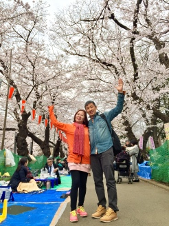 12. My parents posing with the cherry blossoms at Ueno Park. Along the walkways - and underneath the trees - it appears that groups could book spaces for elaborate picnics, where individuals dine on improvised cardboard boxes and feast on a variety of food items.