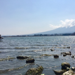 34. Man fishing on an elevated stool, with Mount Fuji in the background.